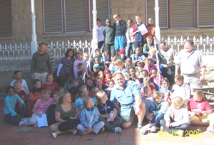 Grant M. Mc Ilrath- A.K.A - The Meerkat Man and Students and Teachers from Port Alfred High School in the courtyard of The CP Nel Museum in Oudtshoorn in the Western Cape of South Africa.